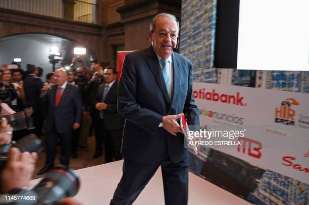 Mexican tycoon Carlos Slim arrives with members of his crew to the VII Symposium of the Historic Center at the Miner's Palace in Mexico City on May...