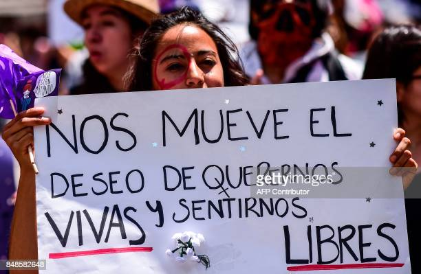 A Mexican woman holding a sign reading We are moved by the desire to love ourselves and feel alive and free takes part in a protest against murders...