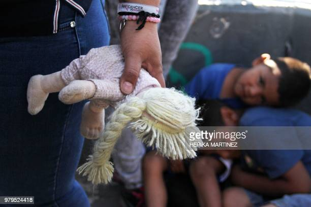 A Mexican woman holds a doll next to children at the Paso Del Norte Port of Entry in the USMexico border in Chihuahua state Mexico on June 20 2018 US...
