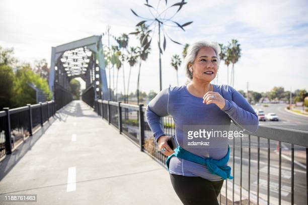 mexican woman jogging on a trail - cardiovascular exercise stock pictures, royalty-free photos & images