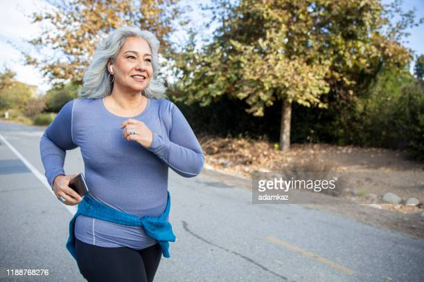 mexican woman jogging - jogging stock pictures, royalty-free photos & images