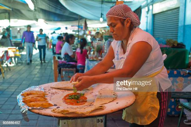 Mexican woman making traditional food in a street food market Oaxaca is known throughout Mexico and internationally for its great food Seen as a...