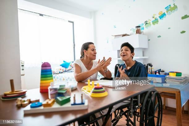 mujer mexicana cantando a su hijo adolescente con parálisis celebral - discapacidad intelectual fotografías e imágenes de stock