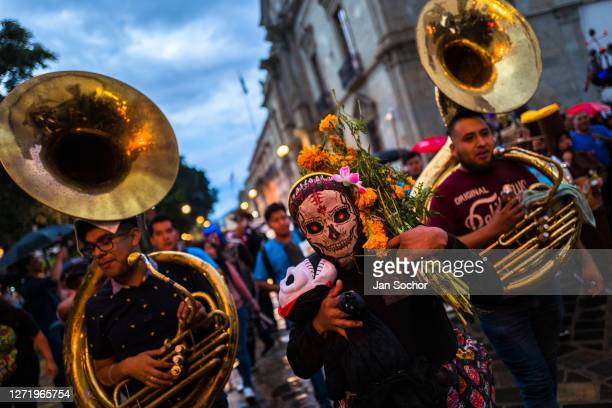 Mexican woman wearing a scull mask and followed by brass band musicians performs on the street during the Day Of The Dead celebrations on October 30...