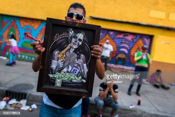Mexican worshiper of Santa Muerte holds religious artwork during a pilgrimage on April 1 2018 in Tepito Mexico City Mexico Santa Muerte is a female...