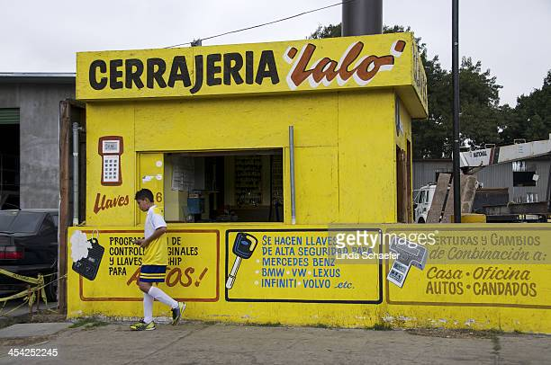 Mexican youth dressed in yellow soccer gear walks past a small shop painted in yellow on his way to soccer practice. Tijuana is a very colorful city...