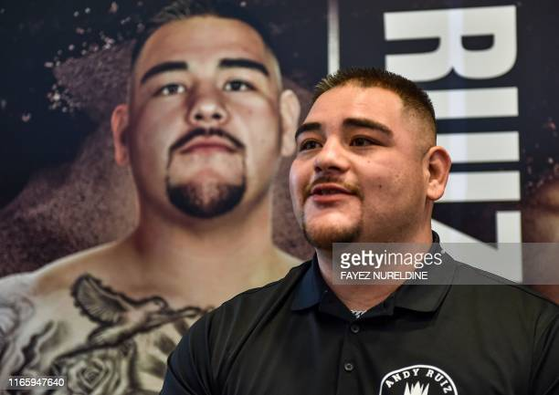 MexicanAmerican heavyweight boxing champion Andy Ruiz Jr poses before a poster of the upcoming Clash on the Dunes fight between him and British...