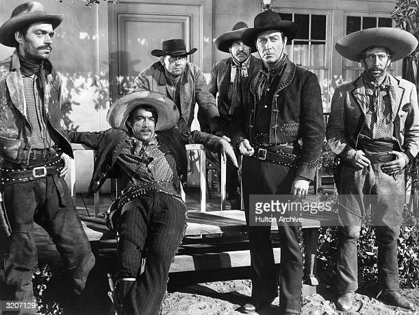 Mexicanborn actor Anthony Quinn leans back against a porch railing wearing a gunbelt and a sombrero as actors Jack Elam Robert Taylor and three other...