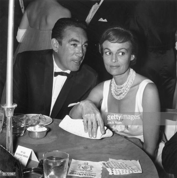 Mexicanborn actor Anthony Quinn leans in to talk to his wife American actor Katherine DeMille at a dining table at the Helpers Charity party Beverly...