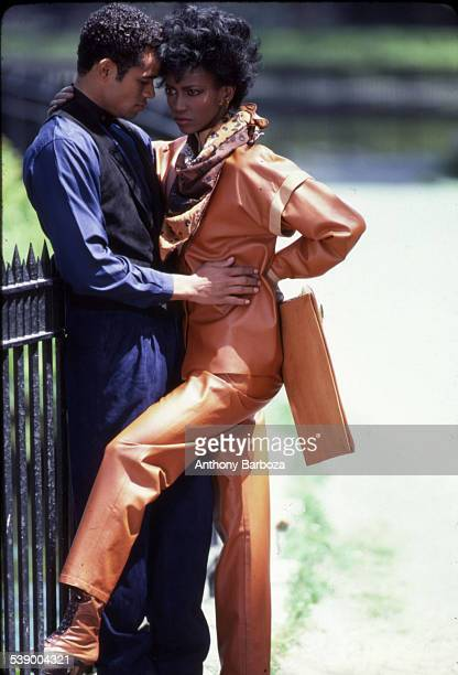 Mexicanborn American actor and director Mario Van Peebles in a blue shirt and black vest poses with an unidentified model in a lightbrown leather...
