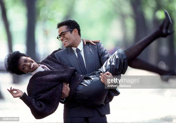 Mexicanborn American actor and director Mario Van Peebles in a grey suit smiles as he carries an unidentified model in a leather skirt and wool...