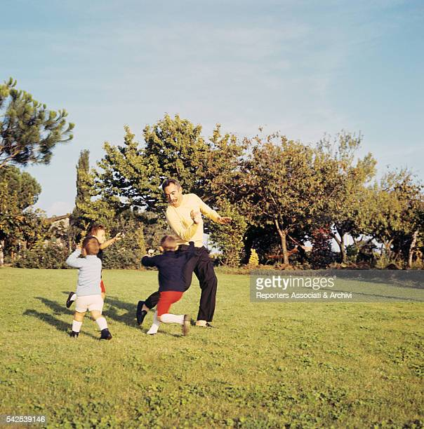 Mexicanborn American actor Anthony Quinn playing in his garden with his three sons 1970s
