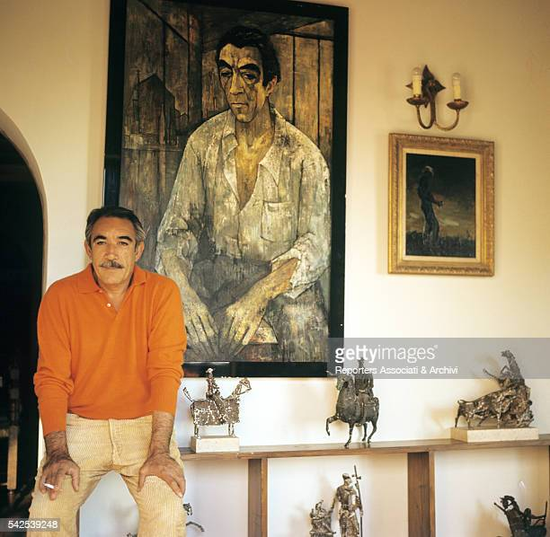 Mexicanborn American actor Anthony Quinn posing in his villa next to a portrait of him 1970s