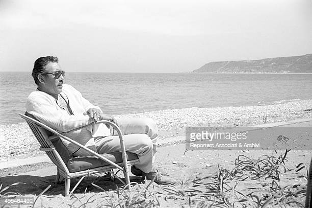 Mexicanborn American actor Anthony Quinn relaxing by the sea during a break on the set of the film The Guns of Navarone 1961