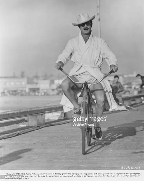 Mexicanborn American actor Gilbert Roland on a bicycle between takes of the RKO film 'The Big Rainbow' later titled 'Underwater' 1954