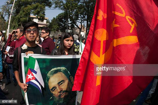 Mexicans gather with Cuban and Mexican national flags a poster of Cuban revolutionary leader Fidel Castro and a communist party flag outside the...