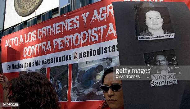 Mexicans hold pictures as tehy demonstrate against the murders and disappearances of journalists in the last years in front of the Attorney's General...