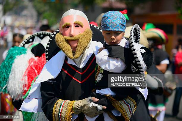 Mexicans wear costumes along the streets of the Penon de los Banos neighborhood in Mexico City on May 5 commemorating the anniversary of Mexico's...