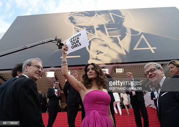 MexicanUS actress and producer Salma HayekPinault holds a cardboard reading '# Bring back our girls' as a sign of support for the kidnapped Nigerian...