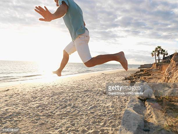 Mexico, Baja California, Man jumping from stone wall onto beach