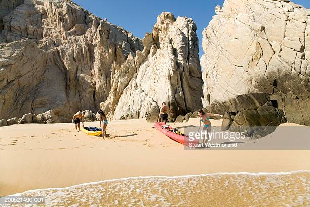 'Mexico, Baja, Land's End, four adults with kayaks on beach'