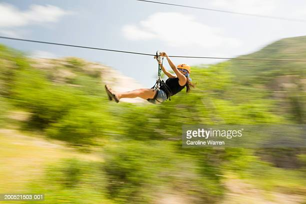 'Mexico, Baja, woman riding zipline in Costa Azul Canyon, side view'