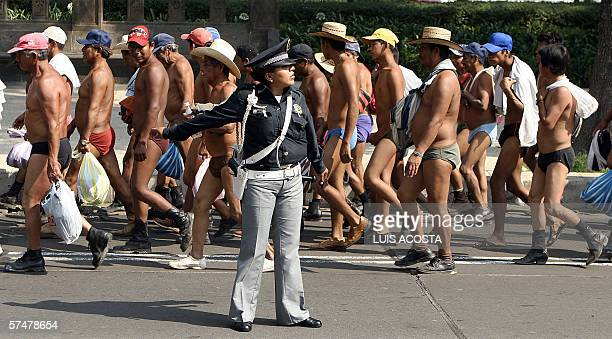 A Mexican policewoman directs the traffic during a march of stripped peasants during a protest by members of the indigenous group '400 Pueblos' at...