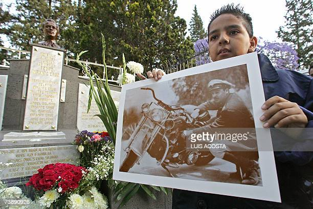 A young fan holds a picture of the late Mexican actor and singer Pedro Infante in front of his tomb during the commemoration of the 50th anniversary...