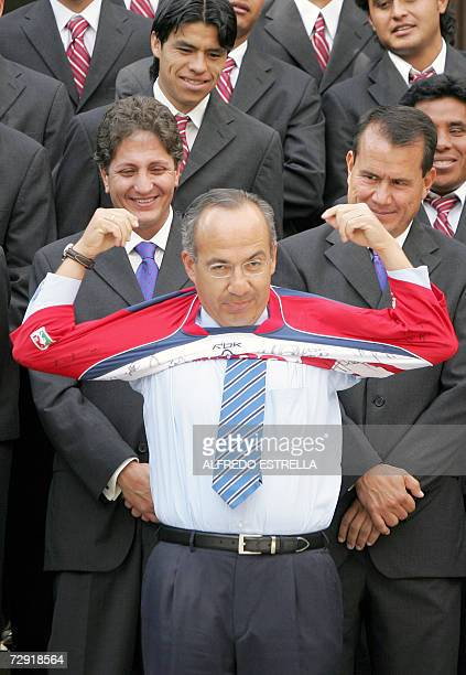 Mexican President Felipe Calderon puts on the jersey of Mexican football team Chivas de Guadalajara accompanied by Jorge Vergara and other team...