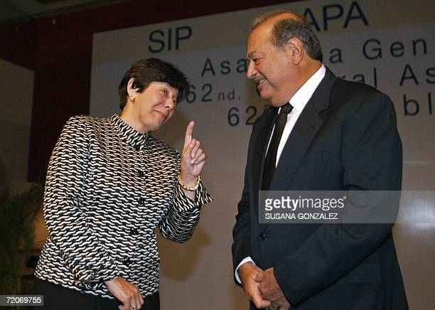 Mexican tycoon Carlos Slim listens to the Inter American Press Society President Diana Daniels during a break of the 62nd SIP assembly in Mexico City...