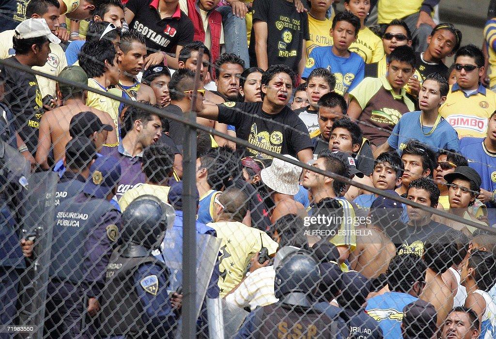Un fanatico de la hinchada de America increpa policias tras haber sido golpeado en la tribuna del estadio Azteca, durante un partido frente a Monterrey valido por la decima jornada del Torneo Apertura 2006 en Ciudad de Mexico el 24 de setiembre de 2006. Marcador final empate a un gol. AFP PHOTO/Alfredo ESTRELLA
