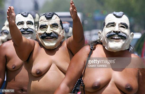 Woman of the indigenous group '400 Pueblos' with masks of Mexican president Vicente Fox march along Reforma Avenue in Mexico City 17 May 2006...