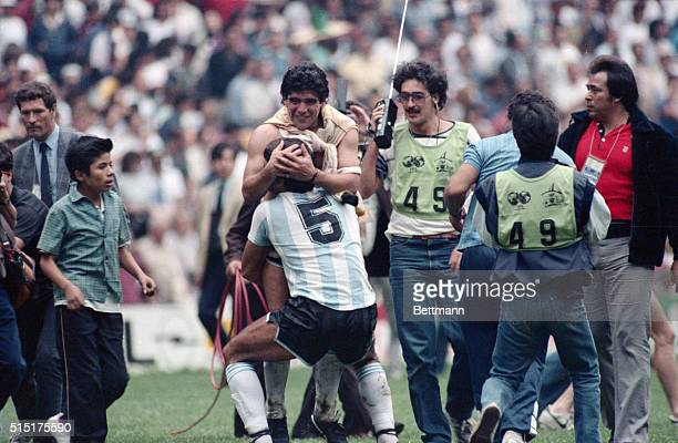 Mexico City: World Cup. Jose Luis Brown hugs argentine team captain Diego Maradona after the World Cup semi final in which Maradona scored both goals...