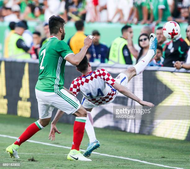 Mexico defender Nestor Araujo left and Croatia forward Duje Cop battle for a ball during the second half of an international friendly soccer game at...
