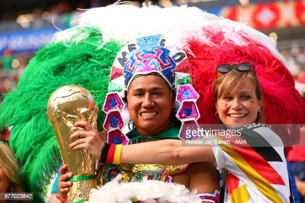 Mexico fan holds a replica World Cup trophy with a female Germany fan prior to the 2018 FIFA World Cup Russia group F match between Germany and...