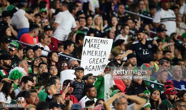 """Mexico fan holds a sign reading """"Mexicans make america great again"""" during the 2019 Concacaf Gold Cup semifinal football match between Mexico and..."""