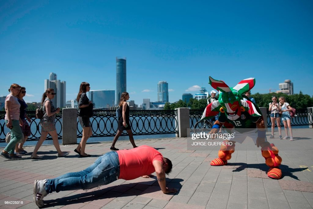 A Mexico fan watches a man make push-ups on a street in Ekaterinburg