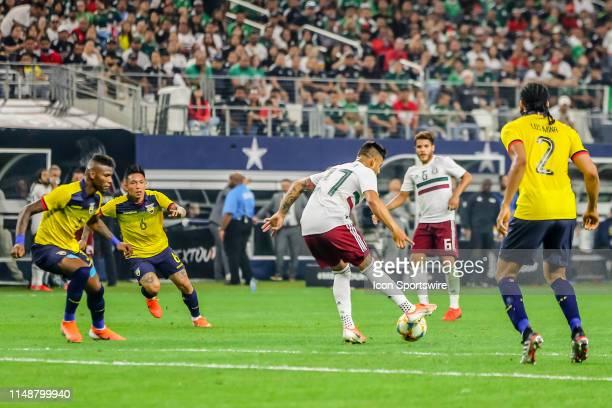 Mexico forward Alexis Vega dribbles the ball through Ecuador defenders during the game on June 09 2019 at ATT Stadium in Arlington Texas