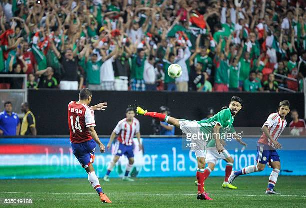 Mexico forward Oribe Peralta vies for the ball with Paraguay defender Paulo Da Silva as fans do the wave in the stands during the friendly match...