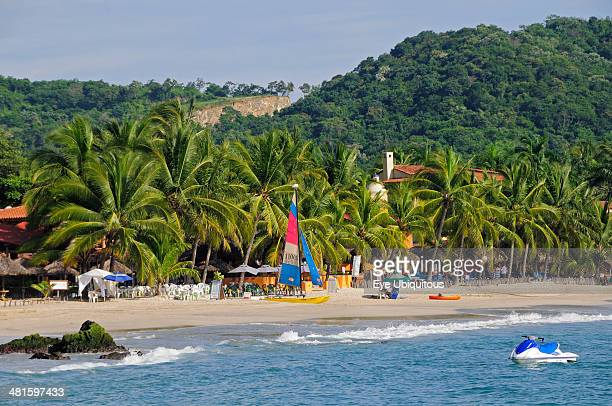 Mexico Guerrero Zihuatanejo View across water towards Playa la Ropa sandy beach lined with lush green palm trees