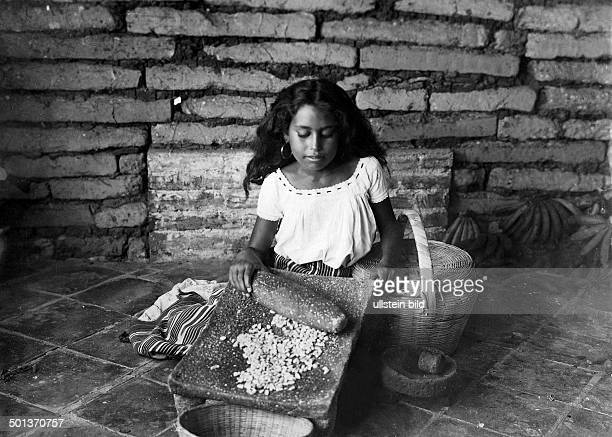 Indian woman milling corn date unknown