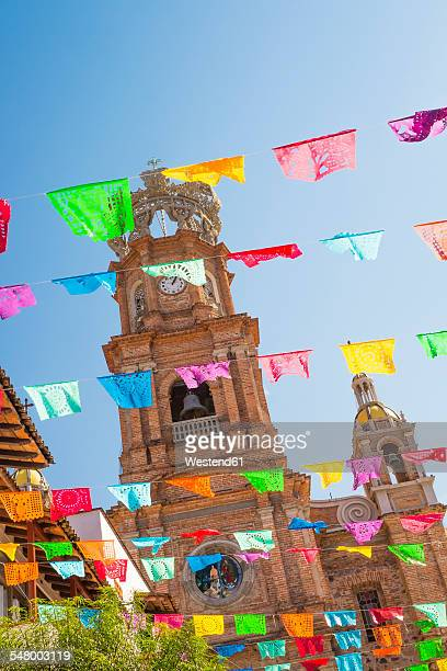 mexico, jalisco, puerto vallarta, colorful flags, tower of the church of our lady of guadalupe in the background - puerto vallarta stockfoto's en -beelden