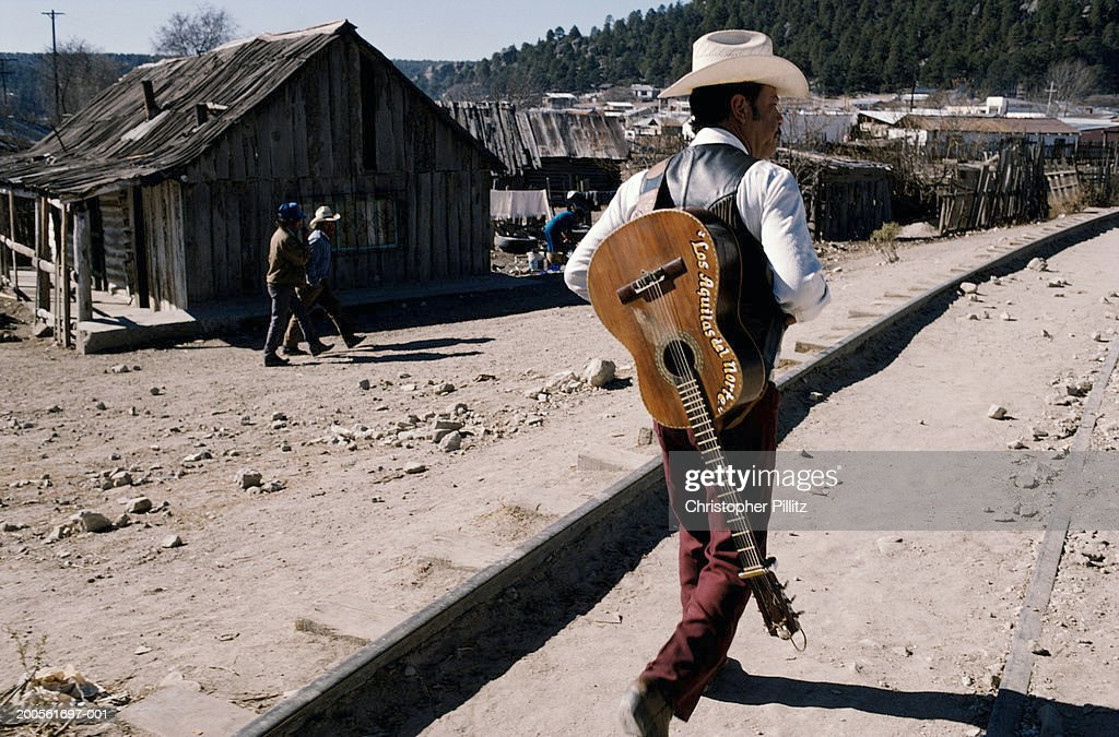 Mexico Man Carrying Guitar On Back Walking Along Railroad Track Stock Photo