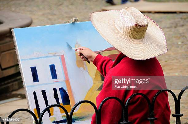 Mexico Michoacan Patzcuaro Painter in Plaza Vasco de Quiroga applying paint to canvas using palette knife
