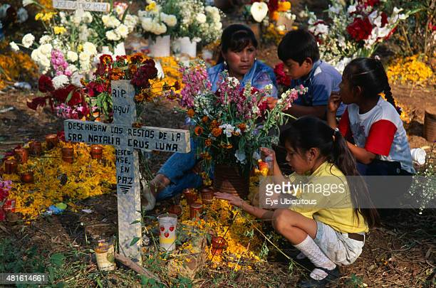Mexico Michoacan Patzcuaro Tzurumutaro Cemetery Children by family grave decorated with candles and flowers for the Day of the Dead