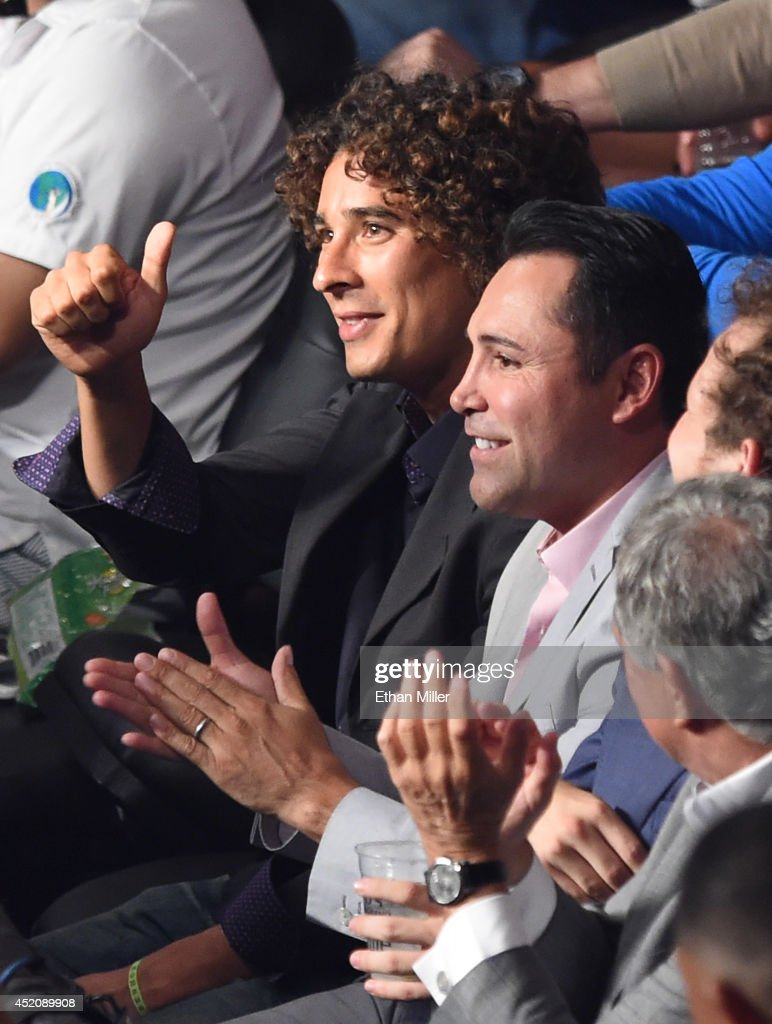 Mexico national soccer team goalkeeper Guillermo 'Memo' Ochoa (L) and President of Golden Boy Promotions Oscar De La Hoya attend the featherweight bout between Abner Mares and Jonathan Oquendo on the undercard of the Canelo Alvarez and Erislandy Lara fight at the MGM Grand Garden Arena on July 12, 2014 in Las Vegas, Nevada.