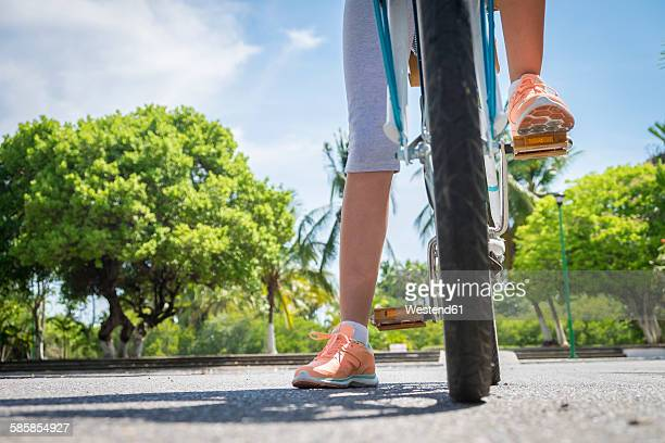 Mexico, Nayarit, legs of teenage girl on a bicycle