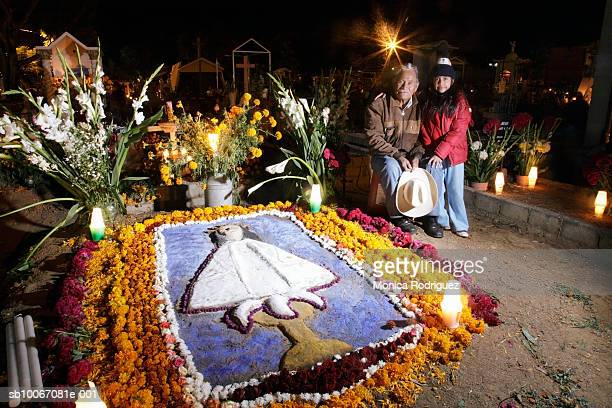 mexico, oaxaca, grandfather with granddaughter (6-7) at cemetery for day of the dead, smiling, portrait - day of the dead stock photos and pictures