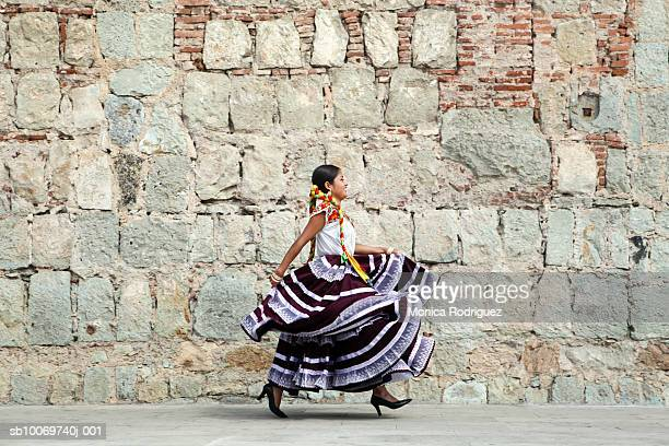 Mexico, Oaxaca, Istmo, young woman in traditional dress walking by stone wall