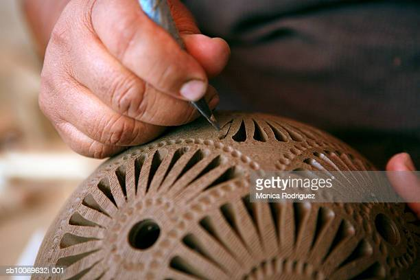 mexico, oaxaca, man making black ceramic decorative pottery, close-up of hands - carving craft product stock pictures, royalty-free photos & images